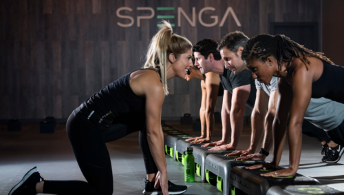Female instructor leading strength training in SPENGA workout class