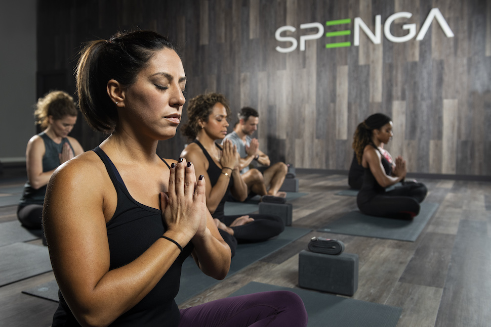 Women with eyes closed and prayer hands sitting cross-legged in yoga pose