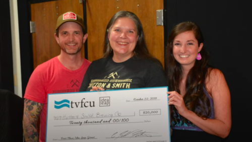 Hutton and Smith Brewing Company employees holding large check from TVFCU