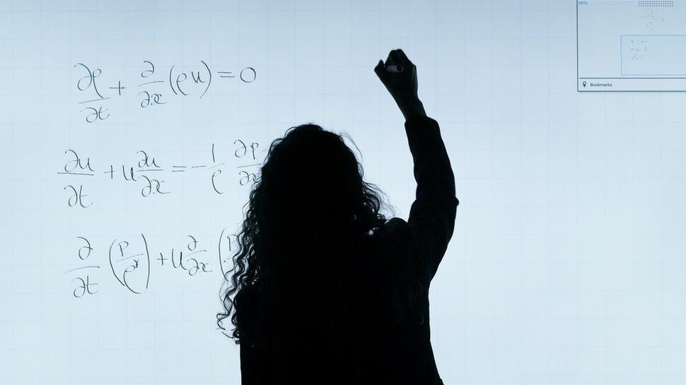 Teacher writing equations with their back turned to a white board.