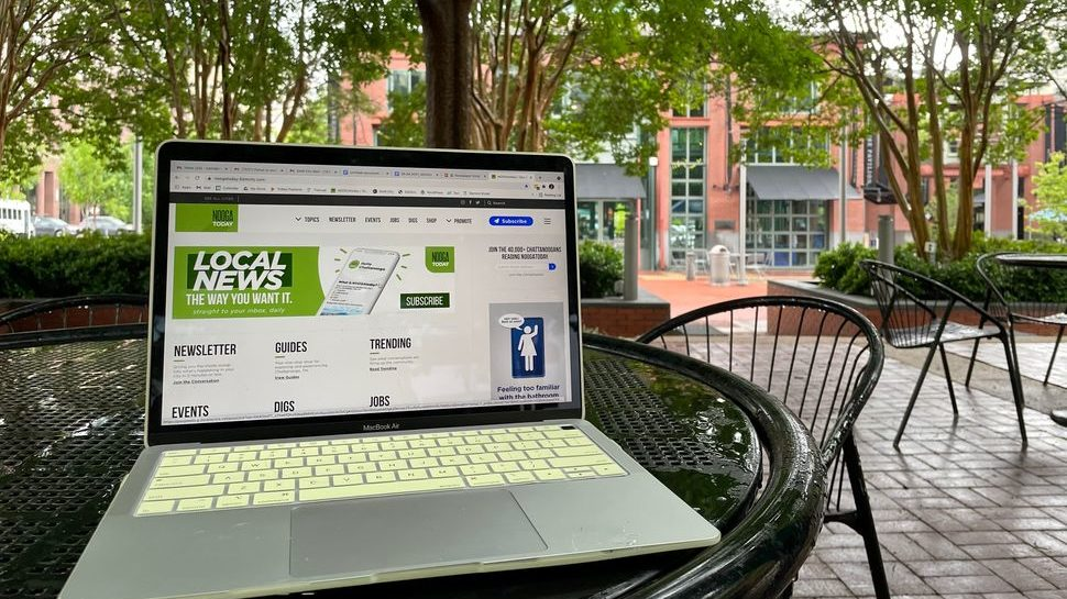 A laptop opened to NOOGAtoday's website front page sitting on a table in a park