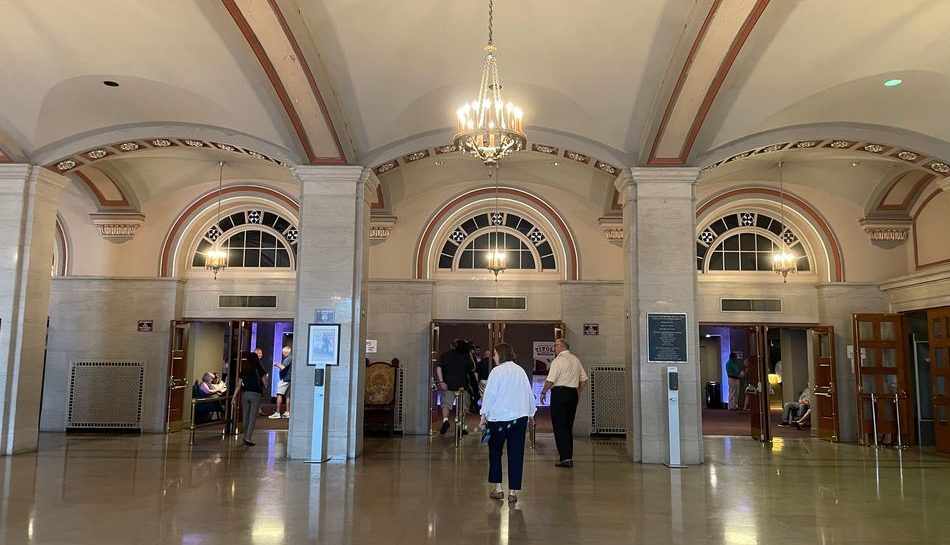 A photo from inside of the Walker Theatre at the main entrance, with a grand chandelier and three main entryways.