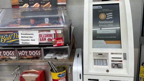 """Photo of an ATM machine displaying the words """"National Bitcoin ATM,"""" located in a gas station next to a hot dog stand."""