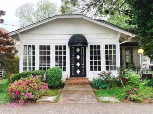 A white bungalow with big windows, a black door and awning + plants and flowers outside