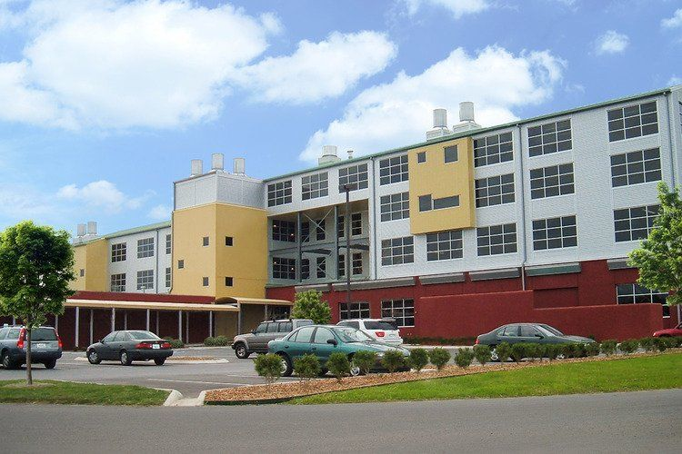 A large yellow and grey building with cars in front.
