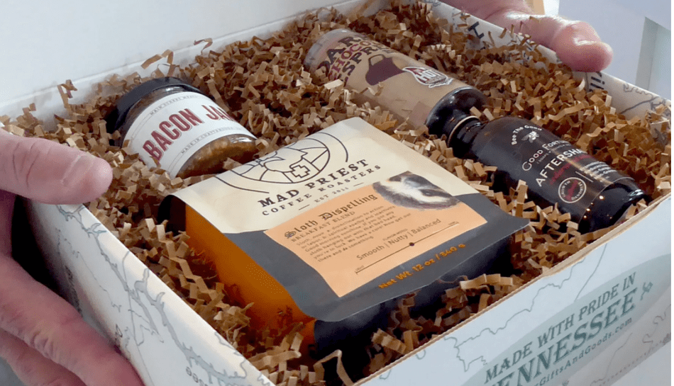 Photo of a gift box filled with Mad Priest coffee, bacon jam, hot cocoa mix, and aftershave.