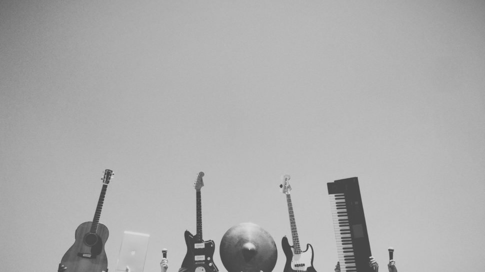 Black and white photo of hands holding up guitars, a keyboard, and symbols.