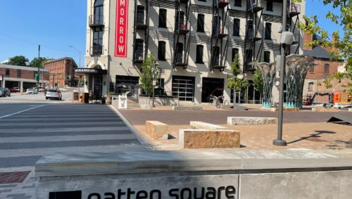 """Photo of a stone bench that reads """"Patten Square"""" on the side, pictured in front of a street with a large apartment complex on the other side."""