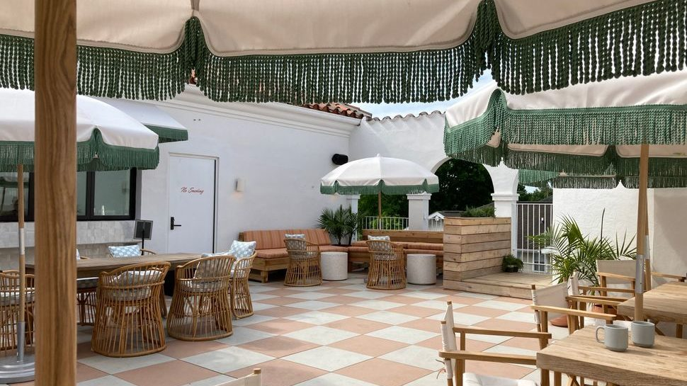 A photo from underneath an umbrella showing a rooftop terrace with outdoor couches + tables under umbrellas, plants, and the side of a white building with a terracotta roof