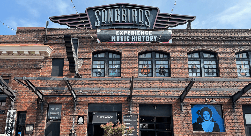 """Photo of a red brick building with stairs leading up to the door and a large sign above the building that reads """"Songbirds."""" There is a smaller sign under this one that reads """"Experience Music History."""""""