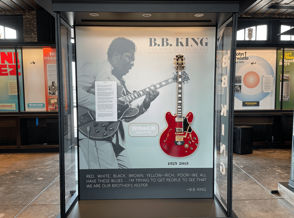 """Photo of a glass display case showing an image of BB King and the words """"BB King"""" displayed prominently. The display case also features a red electric guitar."""