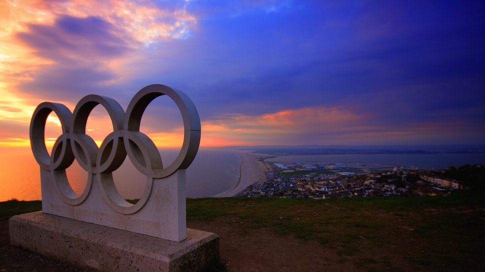 The Olympic rings in front of a colorful sunset