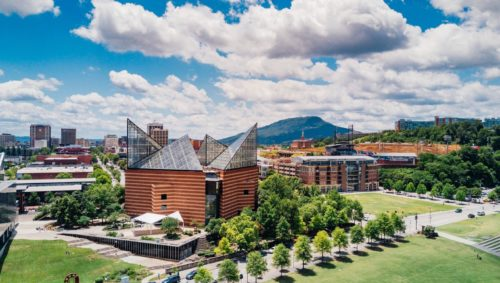 Image of downtown Chattanooga focusing on the Tennessee Aquarium — several red brick buildings with tall, clear triangular geometric roofs.