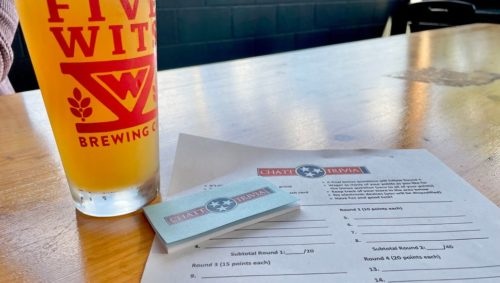 """Photo of a pint of beer with a red logo on it and the words """"Five Wits."""" The beer is sitting on a table with a sheet of paper and a small stack of papers that say """"Chatt Trivia"""""""