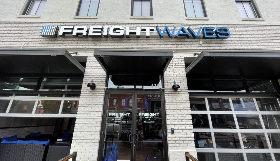 """Photo of the front of the FreightWaves office in downtown Chattanooga. The photo features the front doors to the white brick building and the large """"FreightWaves"""" sign above the doors."""
