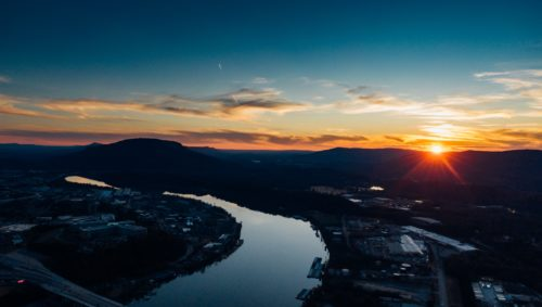 Photo of the Tennessee River at dawn with the sun rising over the mountains in the background.