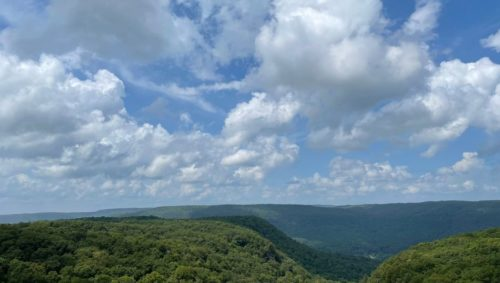 Photo of a green mountain range with a blue sky + clouds