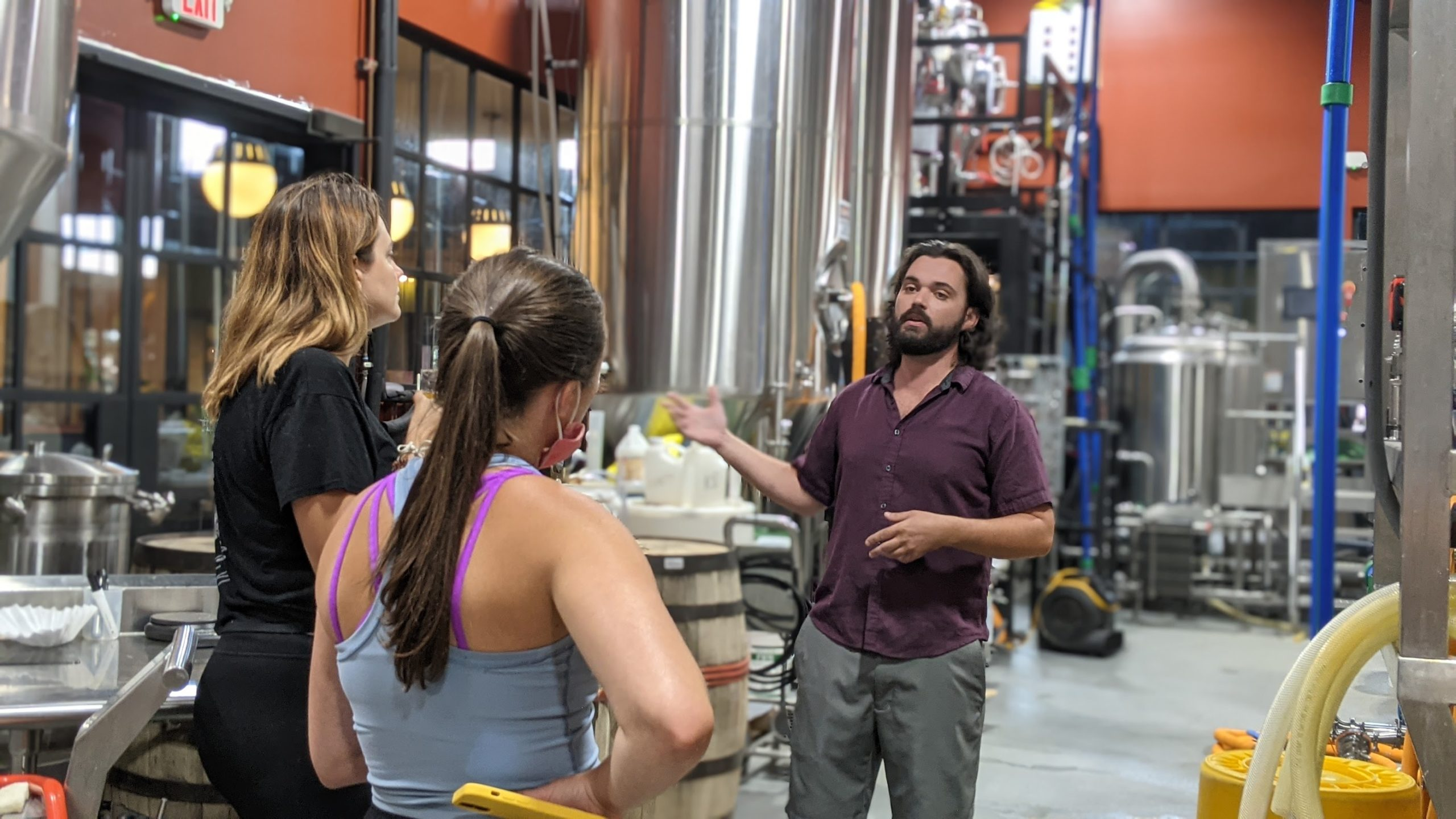 Photo of Brianna and Trista from behind in a brewery, with a brewer giving a tour.