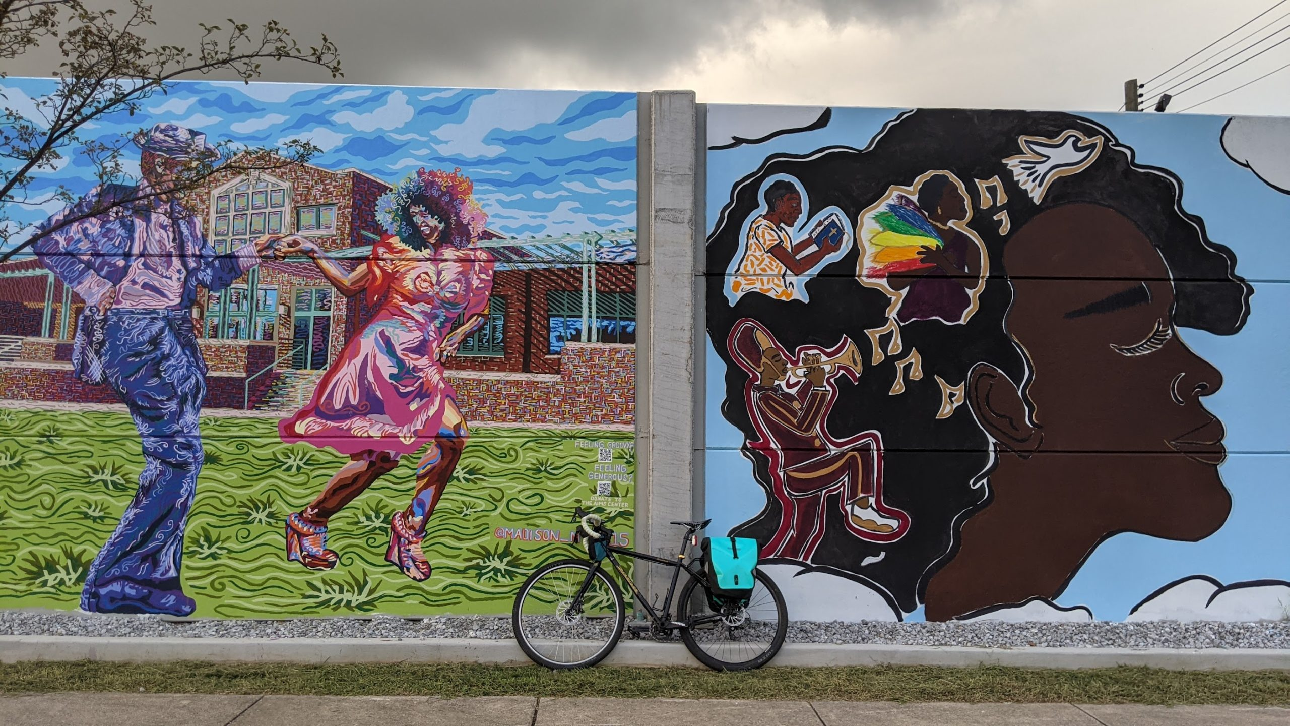 Photo of a bike in front of two large murals. The mural on the left features an interracial couple dancing in front of the Bessie Smith Cultural Center, and the right features a Black woman whose hair is full of different people