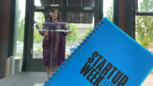 """Photo of a blue notebook reading """"Startup Week 2021"""" held up in front of a woman speaking at a podium"""