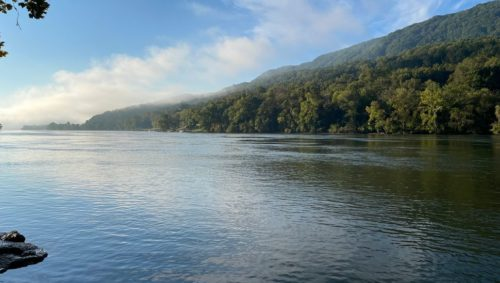Photo taken on the river showing the side of a mountain with wisps of fog.