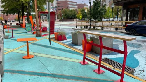 Photo of a sidewalk painted blue and green, lined with red and orange tables and chairs, in addition to a red wing in the middle of the sidewalk. The photo also shows part of a street mural next to the sidewalk that is a geometric design of blues.