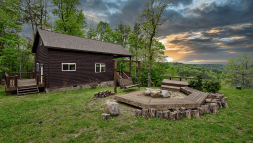 Photo outside of a darn brown cabin, showing a semicircle of seating around a firepit and a view of the sunset over mountains.